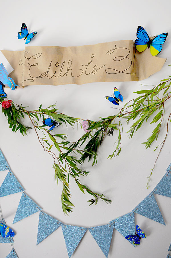 Blue Butterfly Cinderella Birthday Party | DIY Floral Wreath Backdrop with Blue Bunting Banners