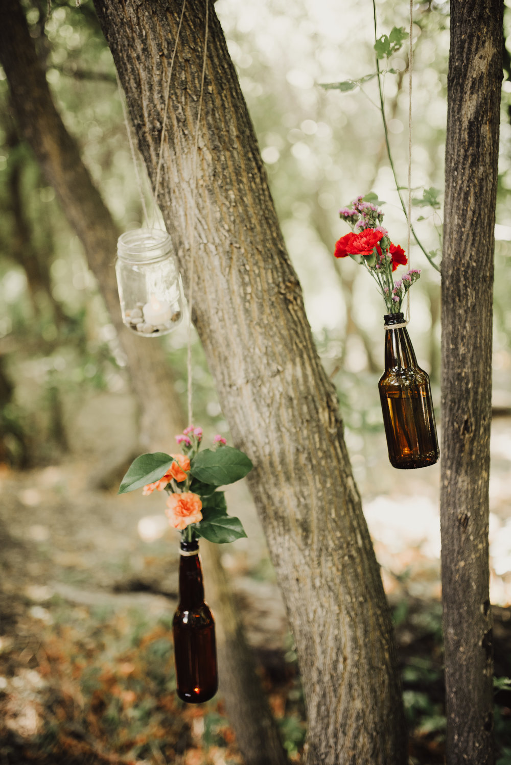 wildflowers-in-jars-hanging-from-forest-trees.jpg
