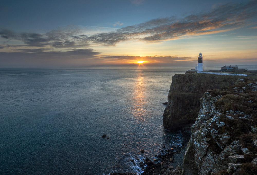 East Lighthouse, with the sun rising over the Mull of Kintyre in Scotland.