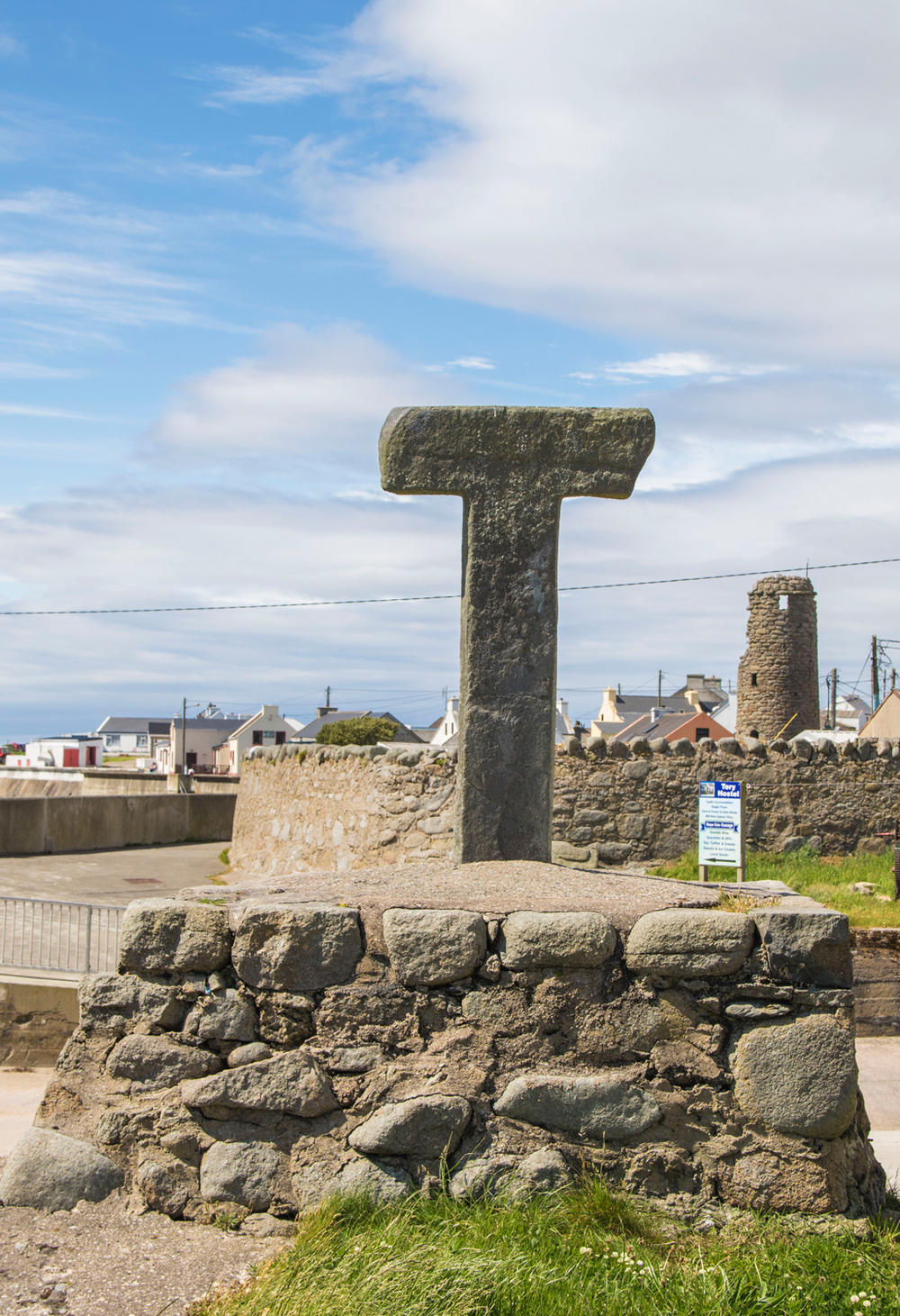 The Tau Cross and in the background, the remains of the Monastery bell tower.