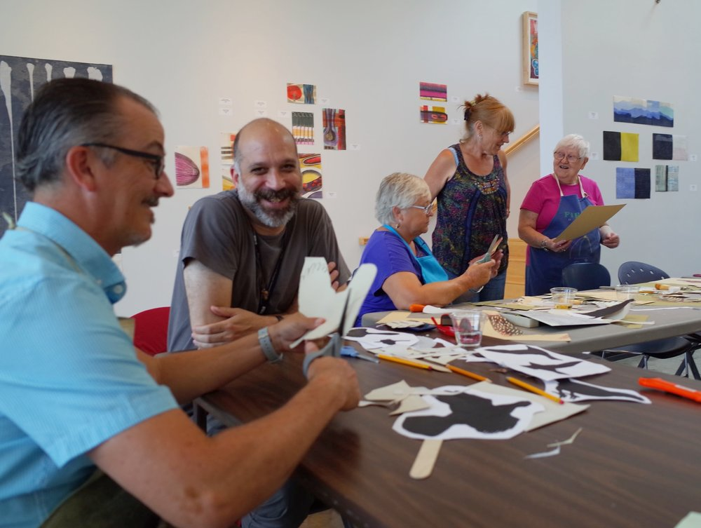 Participants and birdwatchers Jason St. Sauver and Jonathan F. Walz along with members of Karen Kunc's family at the FLOCK Print Action, Constellation Studios, Lincoln, NE July 2015