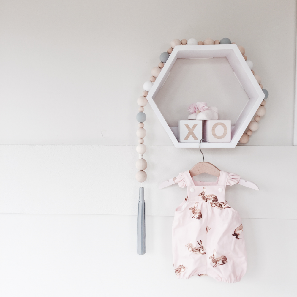 Winnie Dot wooden garland with Whistle Dixie grey tassel, Duke and Duchesses romper on Avery Trend hanger, Peachy Baby blocks, Booties from Italy and Adairs shadow box (painted to suit the room)