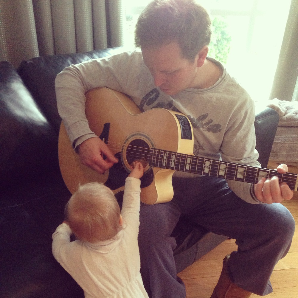 Eve's husband giving their daughter a guitar lesson