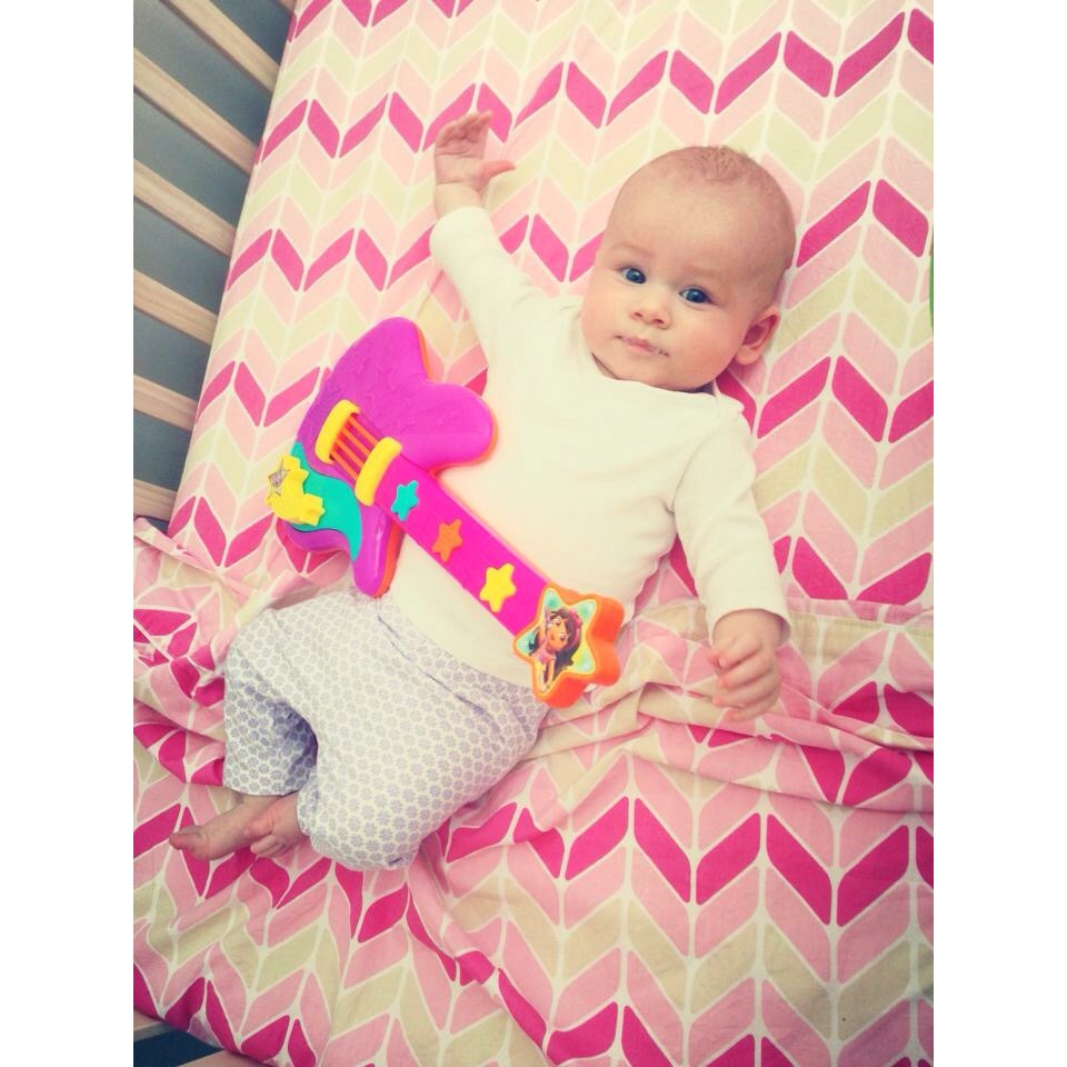 A little Isla rocking out in her cot