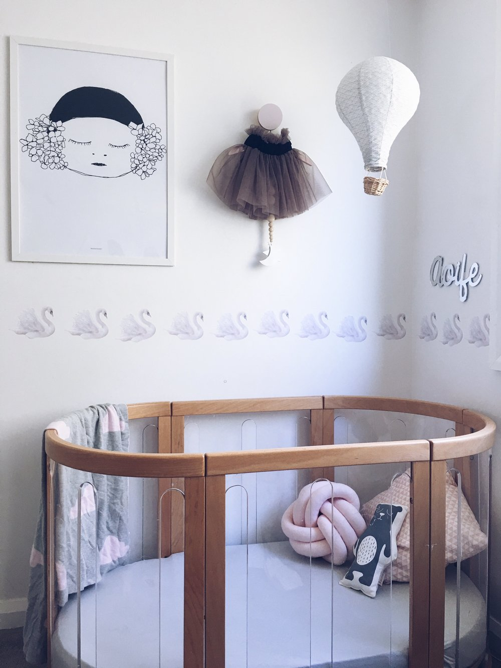 Pax and Hart print, Hubble and Duke skirt and Pocketful Designs drop, Cam Cam lamp shade from Dane Studio, swan decals and mirror name plate from Arlo and Co, cot by Babyhood.