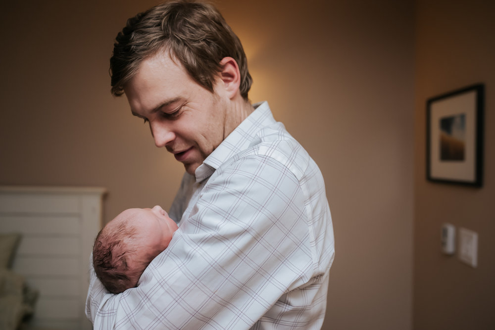 Dad-holds-new-baby-birth-photographer