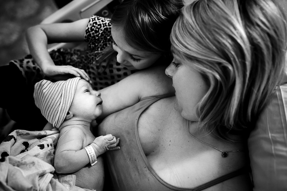 big-sister-admires-baby-birth-photography