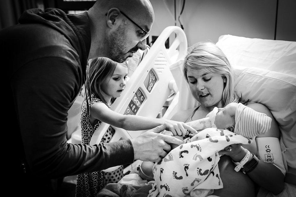 family-admires-new-baby