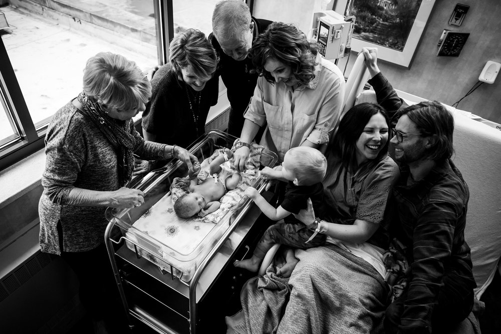 family surrounds new baby