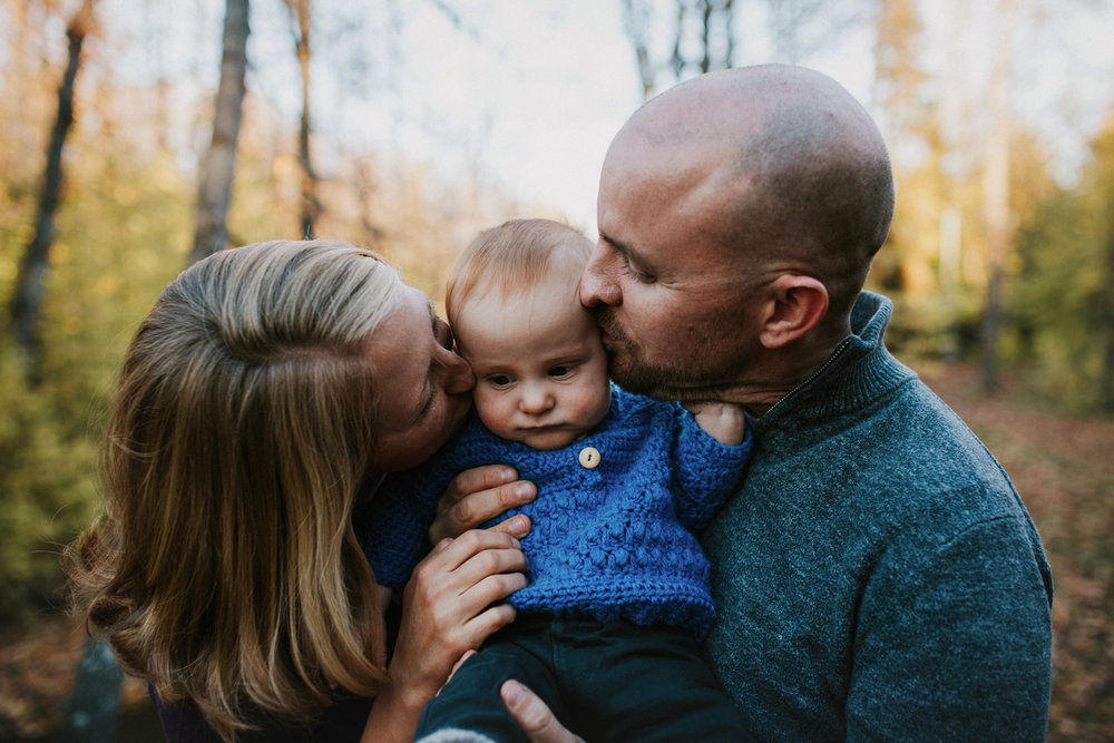 parents kissing baby in anchorage park