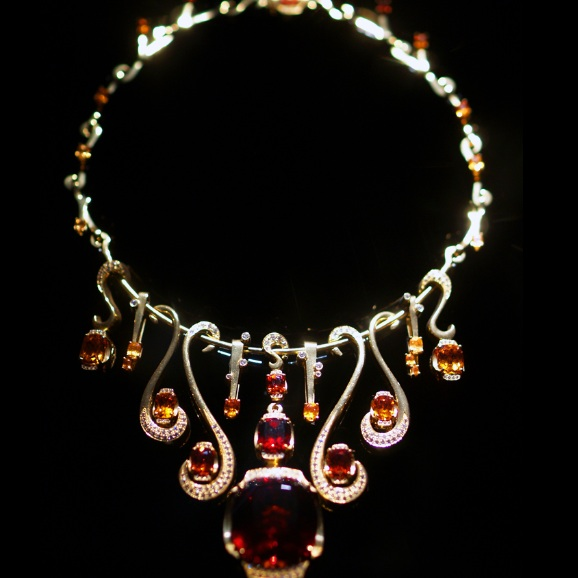 Malaya Garnet  and Diamond necklace by designer Ernesto Moreira, Houston, TX. 22kt Yellow gold necklace with large deep red Malaya Garnet (99 carats) as center stone, (3.015 carats) of pave diamonds, and (50.65 carats) of garnets varying from deep red to bright orange.