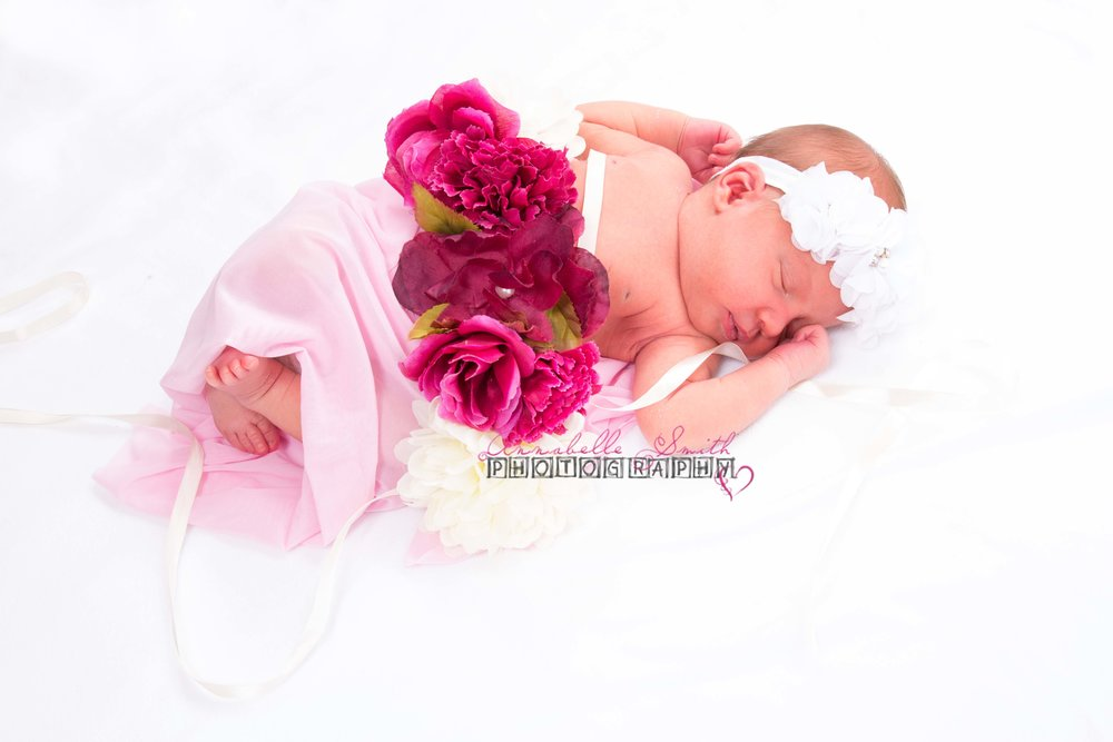 Seven days young wearing the flower accessory her mummy wore during the maternity session