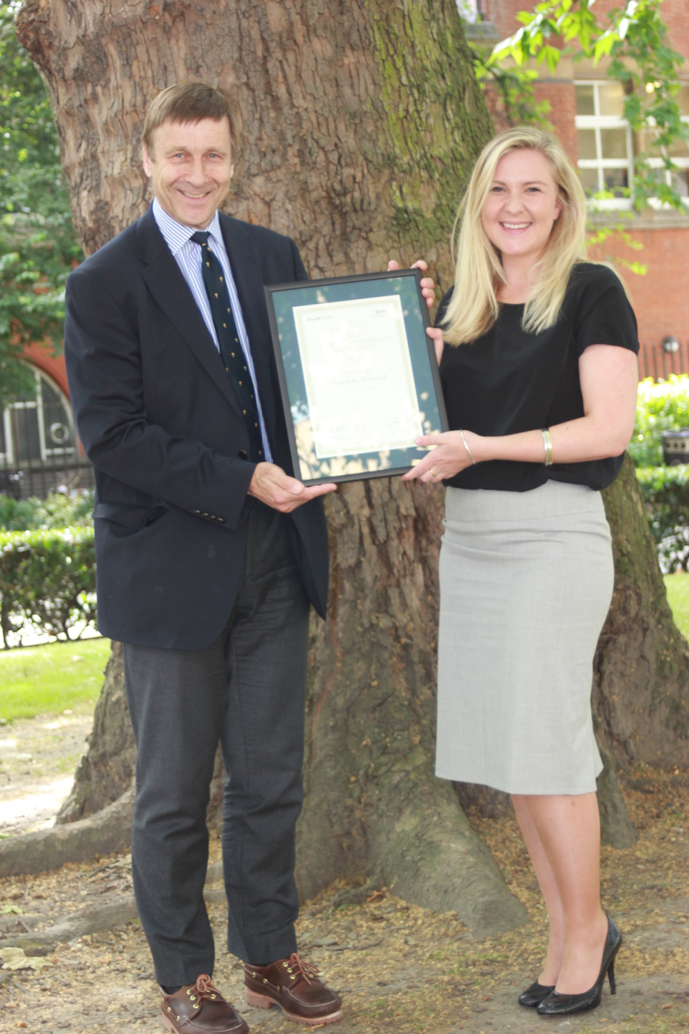 Charlotte Somerville receives her  Cambridge Orthopaedic Writing Prize  certificate from  Mr Richard Villar