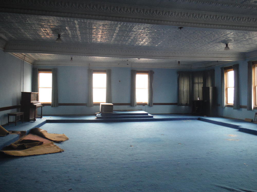 The third floor is still swathed in bright blue, the official color of the Freemasons.  Beneath that thick carpet are the original hardwood floors.  The pressed tin ceiling panels and fixtures are still in remarkably good shape.  Photo by Sydney Haltom, March 2015.