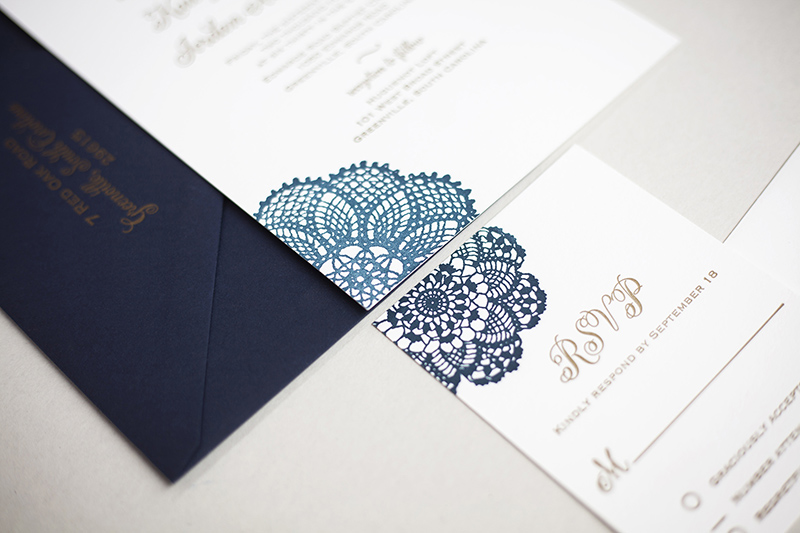 Shades of navy are letterpress printed into a lace doily design for this elegant wedding invitation.