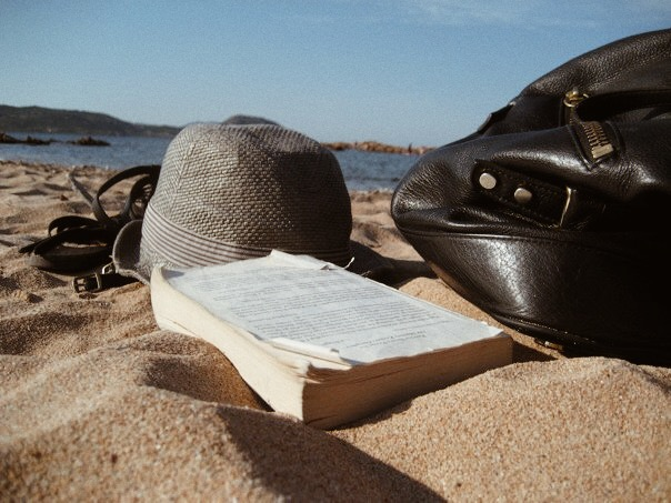 My essentials on a job on Sardinia Island, Italy. Gladiator sandals, a hat for sun protection, a good read, and my tote (also known as my Mary Poppins bag!)
