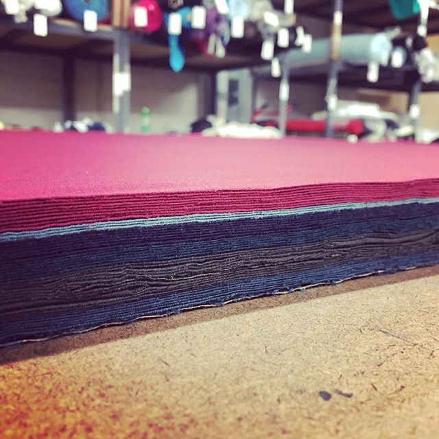 Theres something so satisfying about a nice clean cut through a tall stack of fabrics. #production #productioncutting #apparel #stitchtexas #bessandgeorgeclothing #fabric #madeintexas #apparelindustry #manufacturing