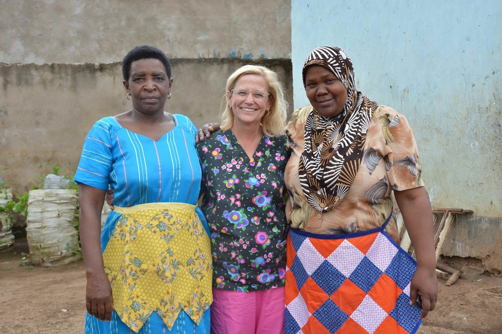 Cathey with Amina and Safael who are wearing aprons handmade by a sweet Mountaintopper.