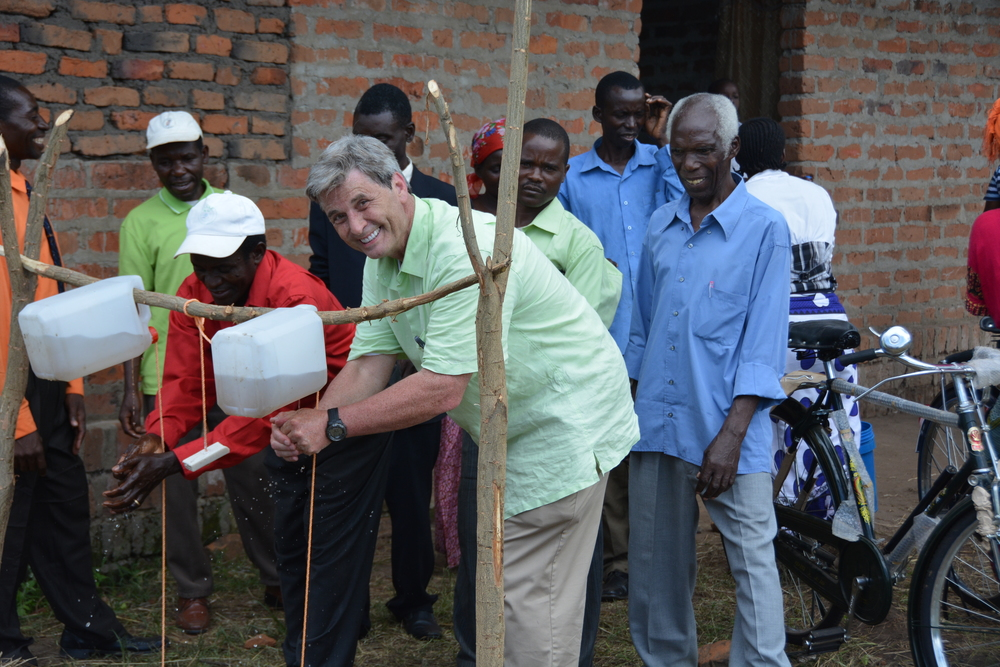 Tanzanian pastors and an American missionary demonstrating the use of handwashing stations- the villagers will follow their lead