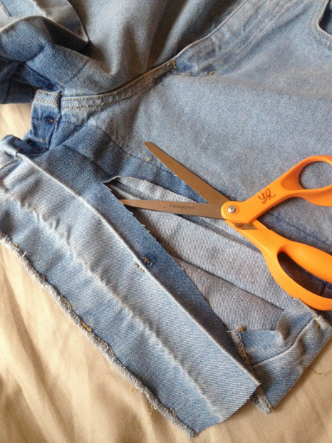 "Take your scissors and cut off all that extra fabric. Here is when you want to try the shorts or jeans on to really decide on the length that you want them. Make sure you cut about 1/4"" LONGER than what you want them to be. This alllows some room for fraying."