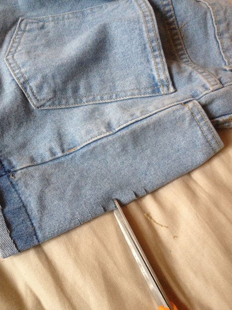"Now find an area of your shorts where you want to place a distressed hole. Fold the fabric in half and make tiny little snips in the shorts about 1/4"" apart."