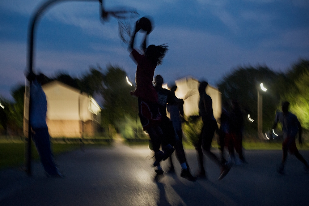 Young men play a game of basketball at the courts next to Jericho Circle.
