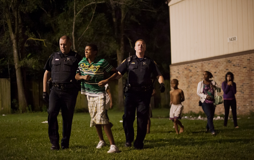 Aurora police carry a young man to an ambulance to continue questioning in after a fight broke out at Jericho Circle. Violence is rare in the community since the city began handing out housing vouchers based on good behavior.