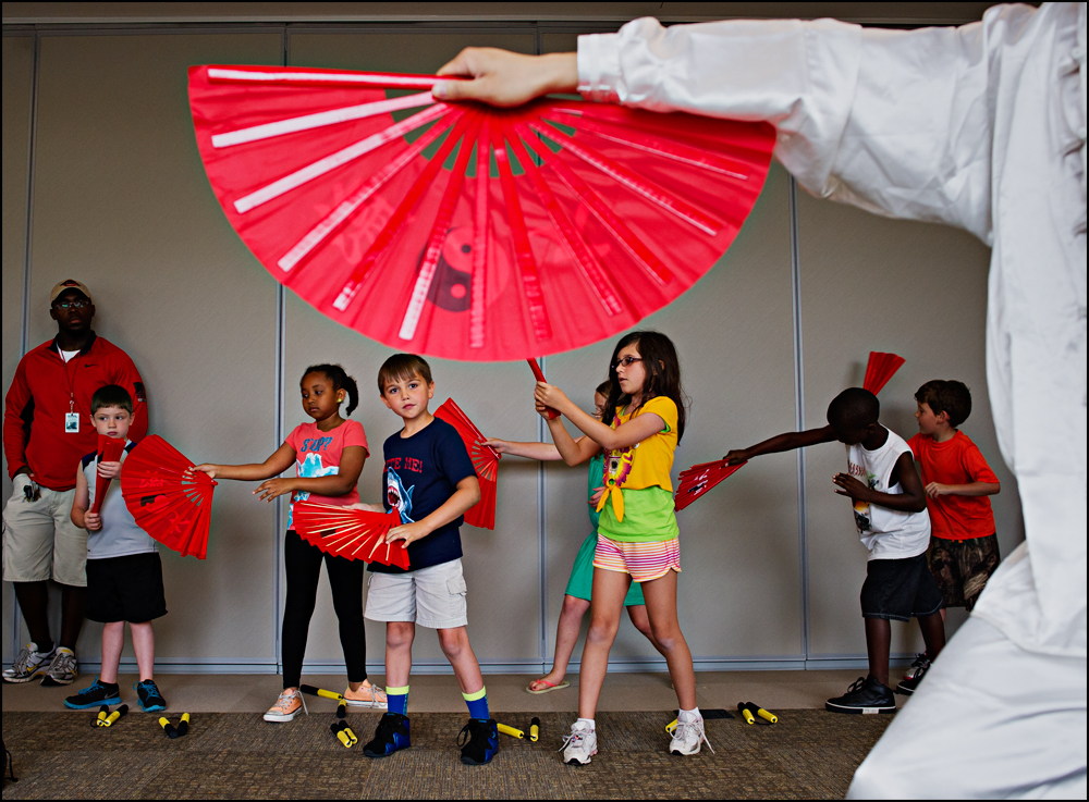 "Dakota Crouch, 7 from Bowling Green, center, watches as Yudian Li, 24 an exchange scholar from China, demonstrates Kung Fu at the Bob Kirby Branch of the Warren County Library in Bowling Green on Thursday, June 5, 2014. The Library kicked off its science-themed summer reading program, ""Spark a Read-action,"" with the Confucius Institute and science demonstrations from Mr. Bond, and The Science Guys. Photo by Brian Powers"