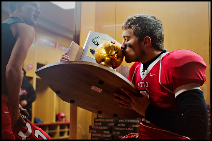 Scott County's Jake Sabol kisses the 6A state championship trophy in the locker room after the Cardinals defeated Meade County tow win the KHSAA Gridiron Bowl at Western Kentucky University in Bowling Green on Saturday, December 7, 2013. Photo by Brian Powers