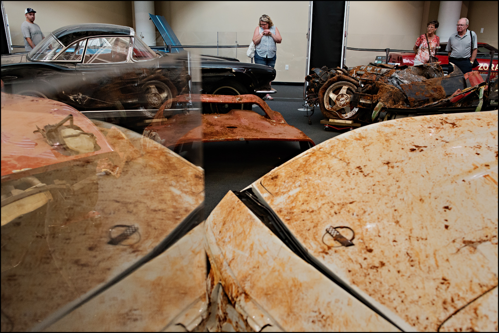 "Visitors including Sue Biddle, center, from Racine, WI, look at the eight cars swallowed by a sinkhole at the National Corvette Museum in Bowling Green on Tuesday, June 24, 2014. ""I'm just amazed they could get these cars out, you could just cry."" Biddle said of the damage done to the classic cars now on display exactly as they were when removed from the hole that opened up on February 12, 2014.