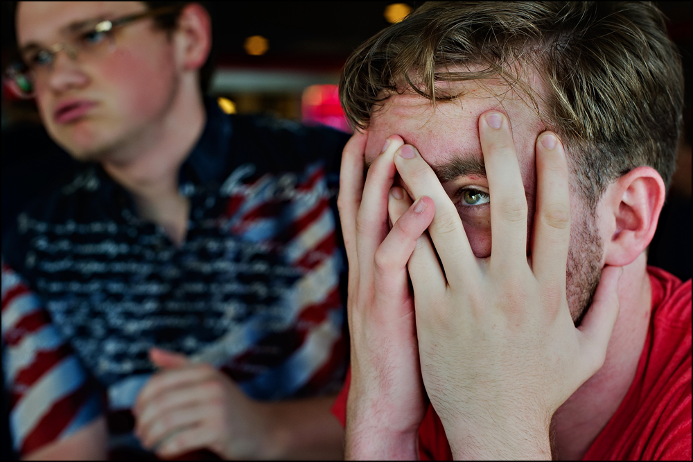 Surrounded by fans at Hilligans Sports bar in Bowling Green, Zach Younglove, 22 of McMinnville, TN, right, reacts after Team USA lost to Belgium 2-1 and was eliminated from the World Cup on Tuesday, July 1, 2014. Photos by Brian Powers