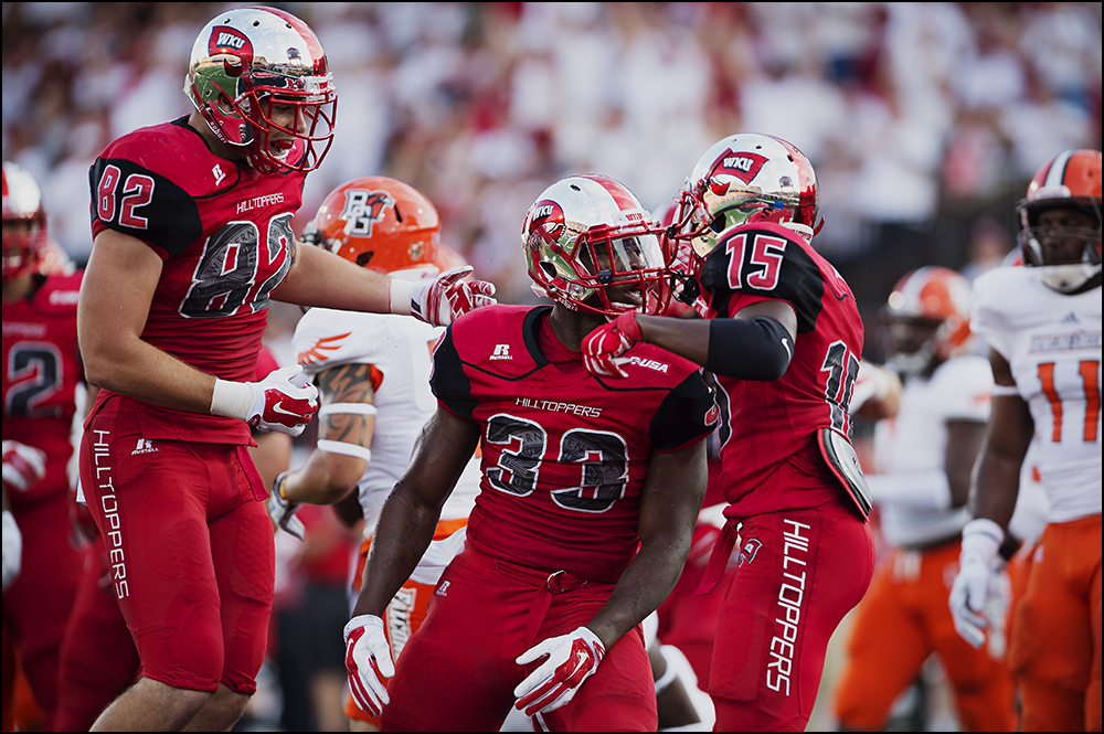 Aug 29, 2014; Bowling Green, KY, USA; Western Kentucky Hilltoppers running back Leon Allen (33) celebrates with teammates tight end Tyler Higbee (82) and wide receiver Nicholas Norris (15) after he scored the first touchdown of the game to take the lead for the Hilltoppers 7-0 at Houchens Industries-L.T. Smith Stadium. Mandatory Credit: Brian Powers-USA TODAY Sports