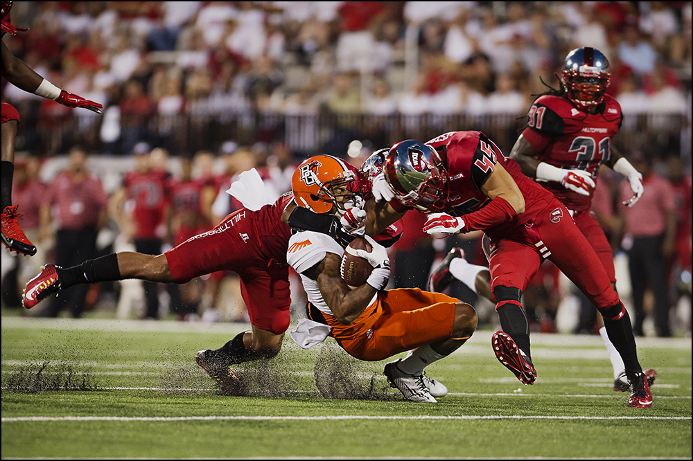 Aug 29, 2014; Bowling Green, KY, USA; Bowling Green Falcons wide receiver Roger Lewis, center, is tackled by Western Kentucky Hilltoppers defensive back Branden Leston (45) and Ricardo Singh (38) during their game  at Houchens Industries-L.T. Smith Stadium. The Hilltoppers would go on to win 59-31. Mandatory Credit: Brian Powers-USA TODAY Sports