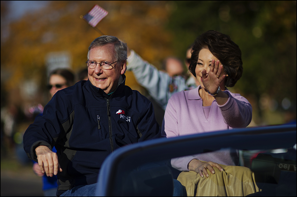 Senate minority Leader Mitch Connell, left, waves to parade watchers with his wife Elaine Chao, right, as they ride in the 50th annual Veteran's Day Parade in Madisonville, Ky. on Sunday, November 2, 2014. Brian Powers/Special to the Courier-Journal