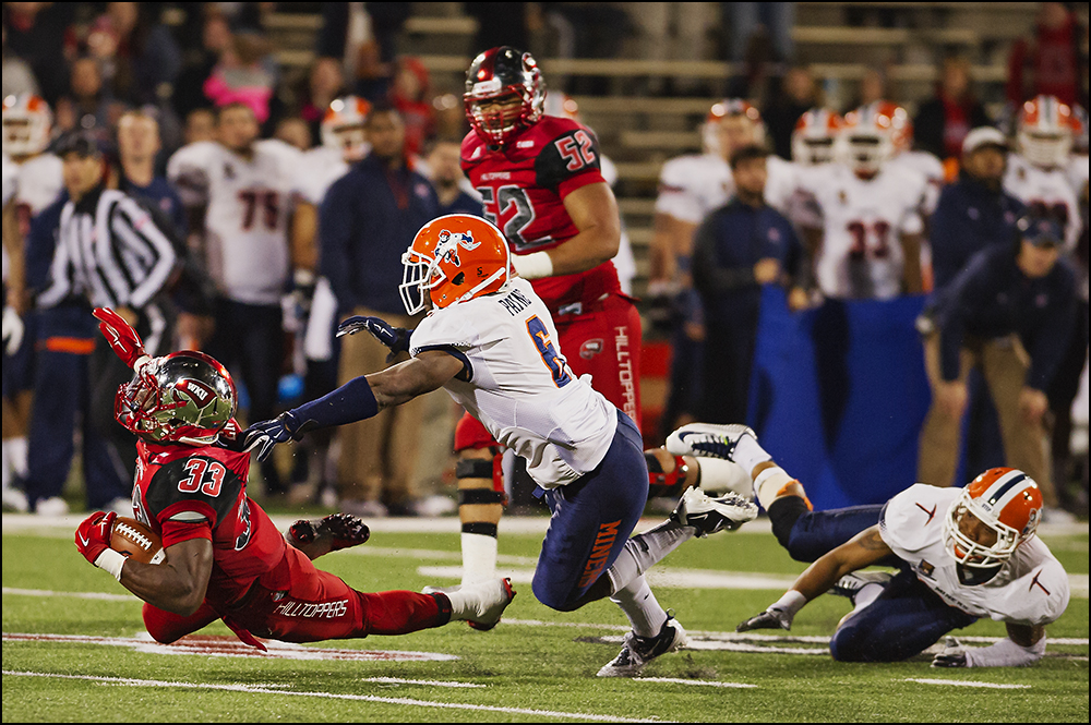 Nov 8, 2014; Bowling Green, KY, USA; Western Kentucky University running back Leon Allen (33) is tripped up by UTEP defensive back Damian Payne (6) at Houchens Industries-L.T. Smith Stadium. WKU won 35-27. Mandatory Credit: Brian Powers-USA TODAY Sports
