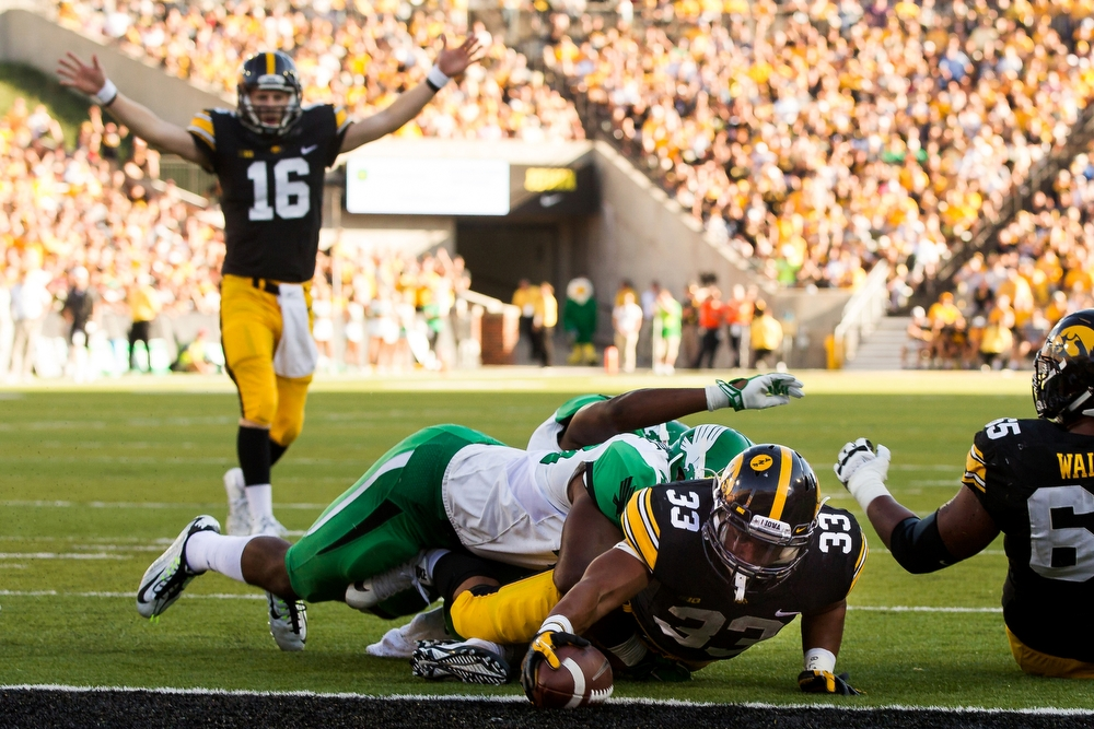 The Iowa Hawkeyes Jordan Canzeri dives for a touchdown as quarterback C.J. Boatyard celebrates in the background during their game against North Texas at home on Saturday, September 26, 2015. Iowa would go on to win 62-16.