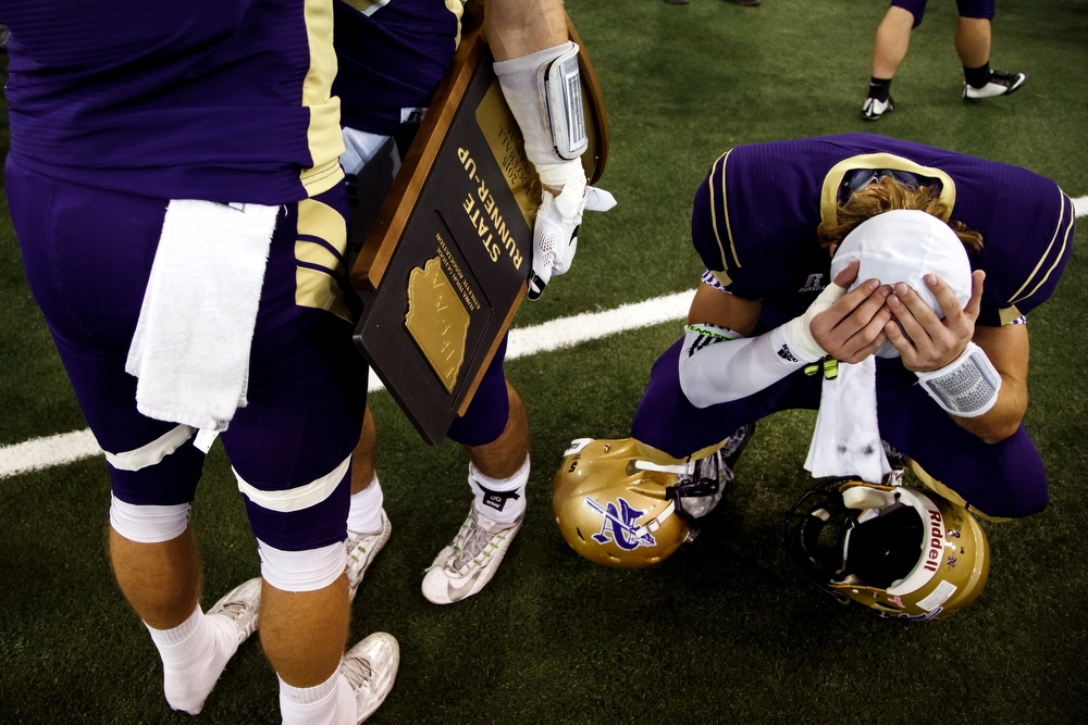 Norwalk's Devin Pickle, right, holds his head after loosing to Pella, 17-31 in the class 3A state championship game at the UNI-Dome in Cedar Falls on Thursday, November 19, 2015.
