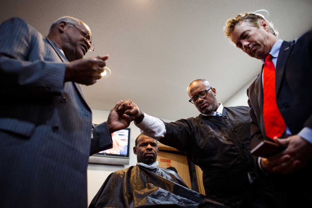 Elder Sylvester Simmons of Waterloo, left, prays for Republican presidential candidate Rand Paul, right, with Hairport barbershop owner Trent Keller, center right, and Herlie Johnson, 37 of Waterloo, center left, during a campaign stop at the Hairport Barber shop on Saturday, December 05, 2015 in Waterloo.