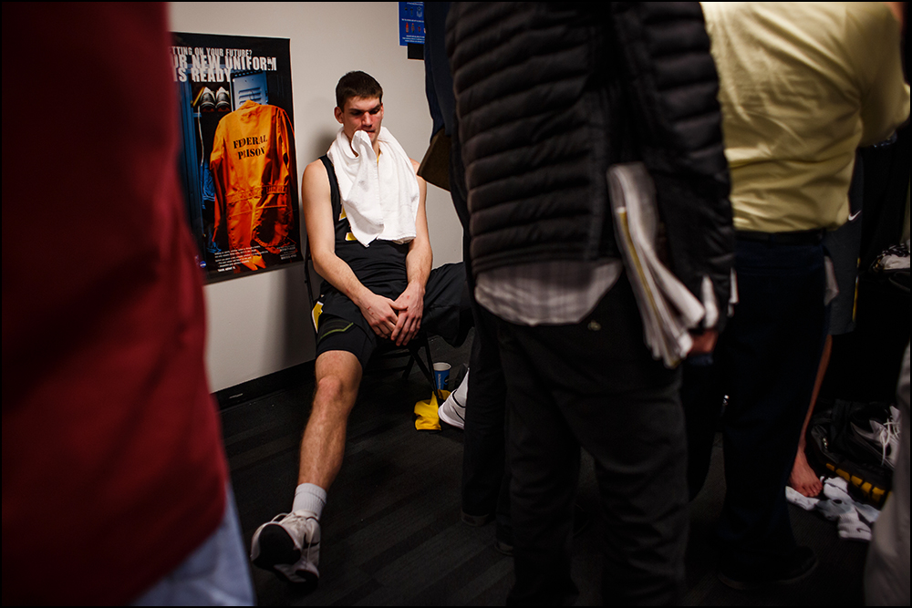Iowa's Adam Woodbury (34) sits in the locker room as media members ask his teammates questions after their 87-68 loss to Villanova at their second round NCAA Basketball Championship game on Sunday, March 20, 2016 in New York City, New York.