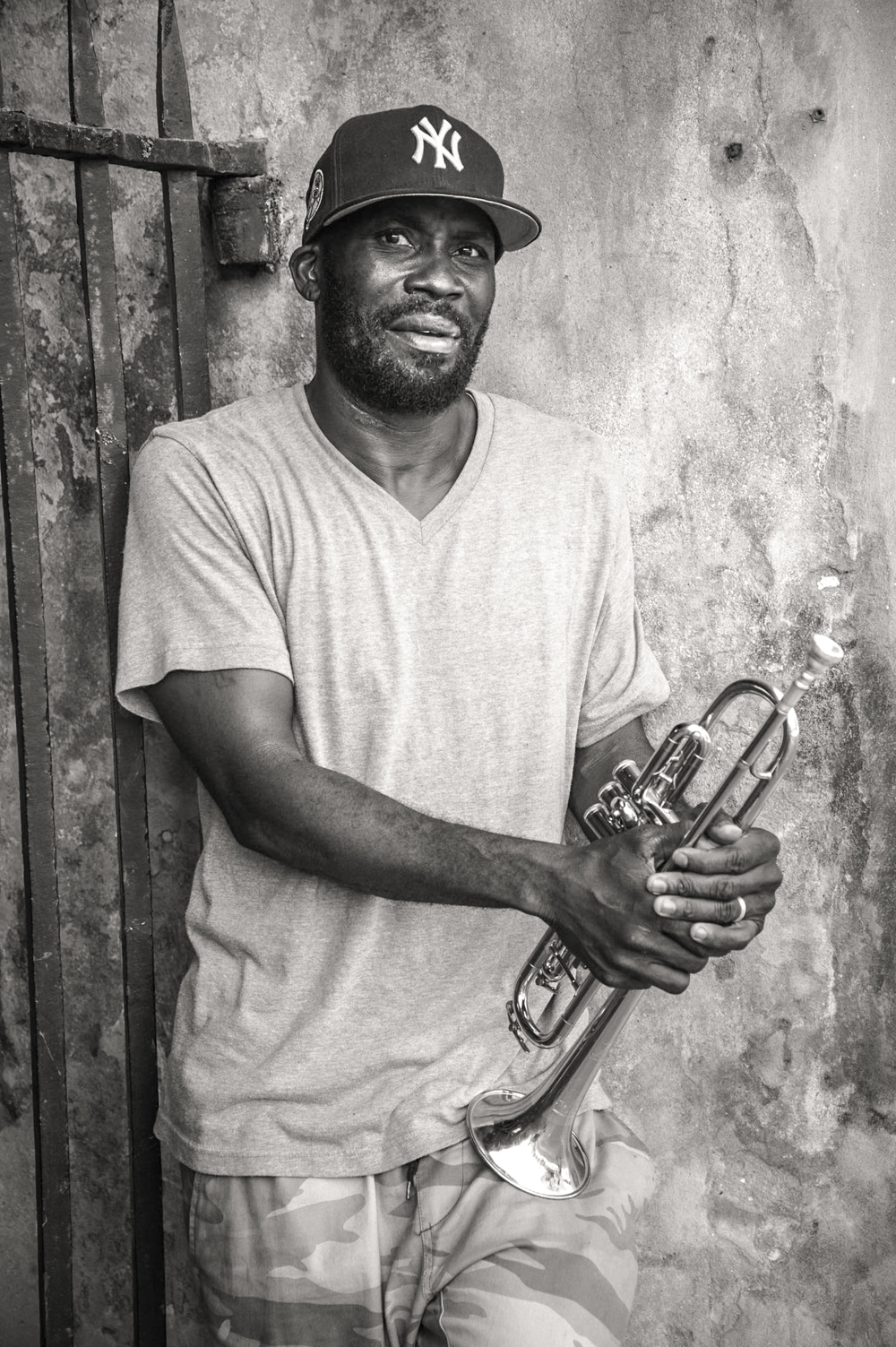 "Glen Andrews - Trumpeter |  New Orleans, LA -  I stood in jackson square and I watched him play for a good 10 to 15 minutes and I just knew I had to shoot his portrait. Photography allows and encourages passionate people watching (at least that's what I tell myself). When he reached a break, I approached him, ""Hey man, I'm a photographer would it be cool to take a photo of you?"" ""Yeah, sure."" he replied. I saw a spot underneath an overhang  with a weathered wall and rusting iron gate making the perfect corner. It had to be in black and white. ""I don't know, maybe bring your trumpet up somehow. Rest it."""
