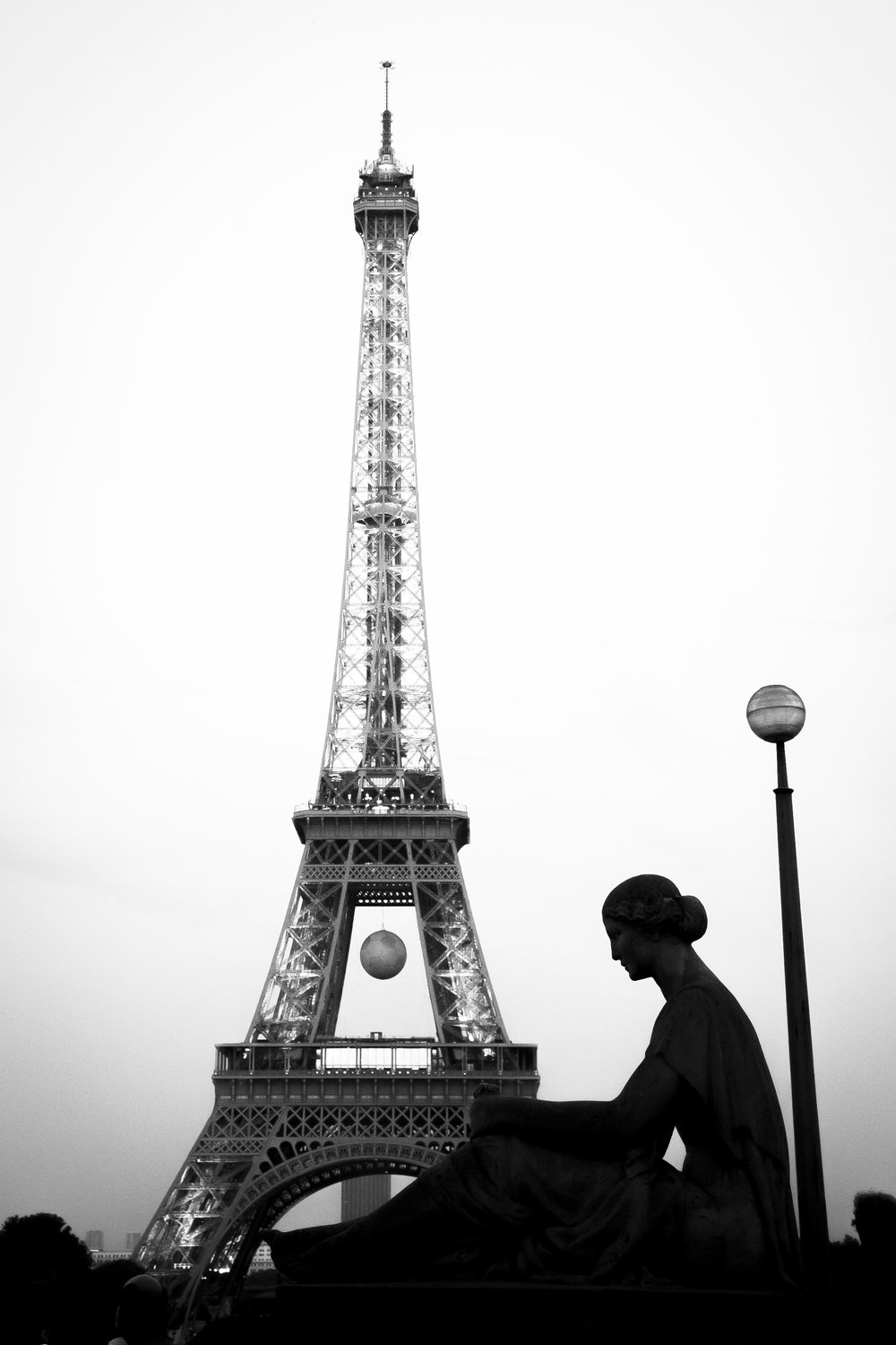"An Image for a Friend | Paris, France - On my first trip to Paris, I stood at the Trocadéro and found a view of the ""Waiting Woman"" statue with the Eiffel Tower beyond. I would edit it much later, turning it to black and white and a heavy silhouette. I did not expect to be so moved by it. A friend from college, who used to live in Paris, gave me some great recommendations before my travels abroad. When the image was complete, I knew it was a gift for her. A shot forever dedicated to my friend, Emily."