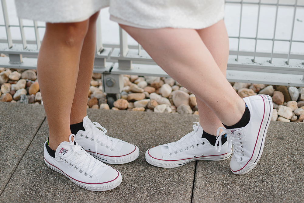 Brides wearing matching white Converse shoes during wedding in DC