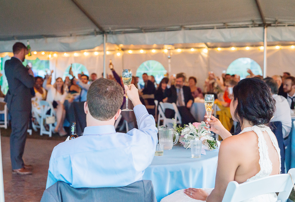Best man gives wedding toast as bride and groom look on during sunset