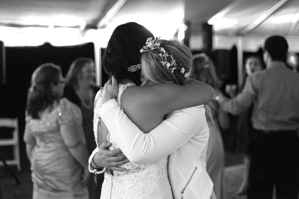 Bride and maid of honor hugging on the dance floor at Rosedale Manor in Greenwell State Park