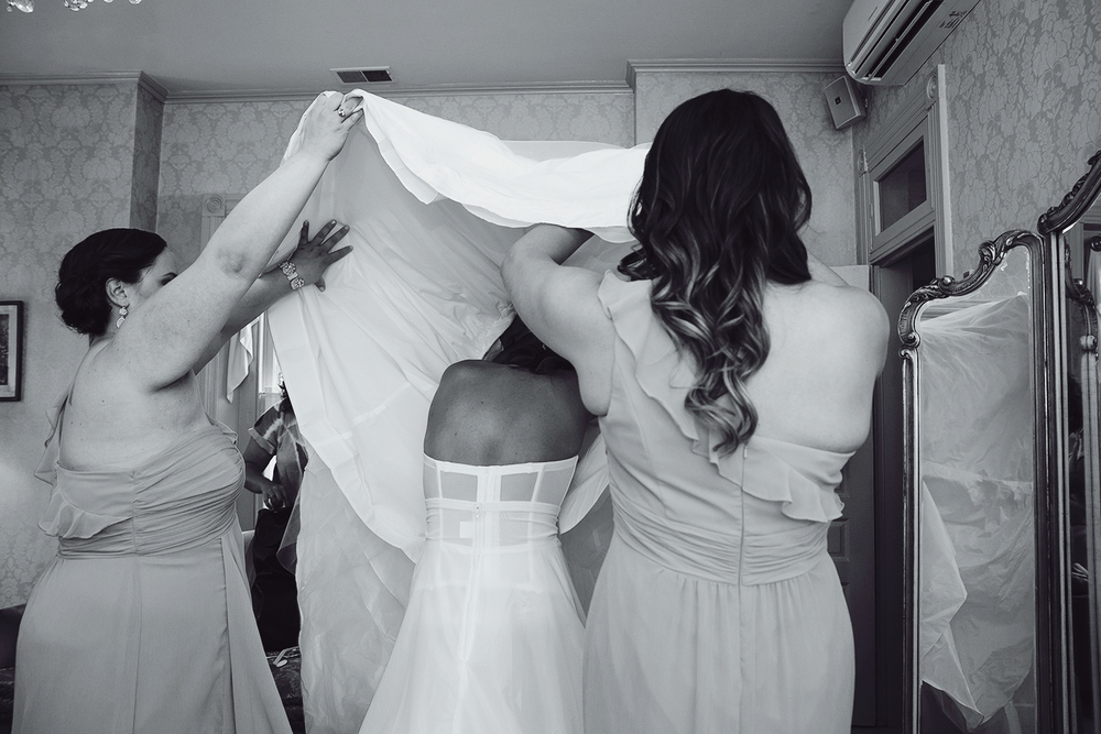 Bride putting on her dress in getting ready suite at Ceresville