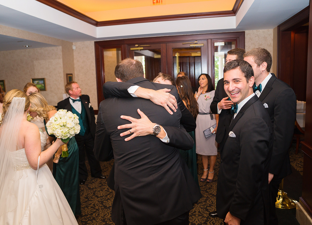 Guests hugging bride and groom one entryway at Springfield Country Club