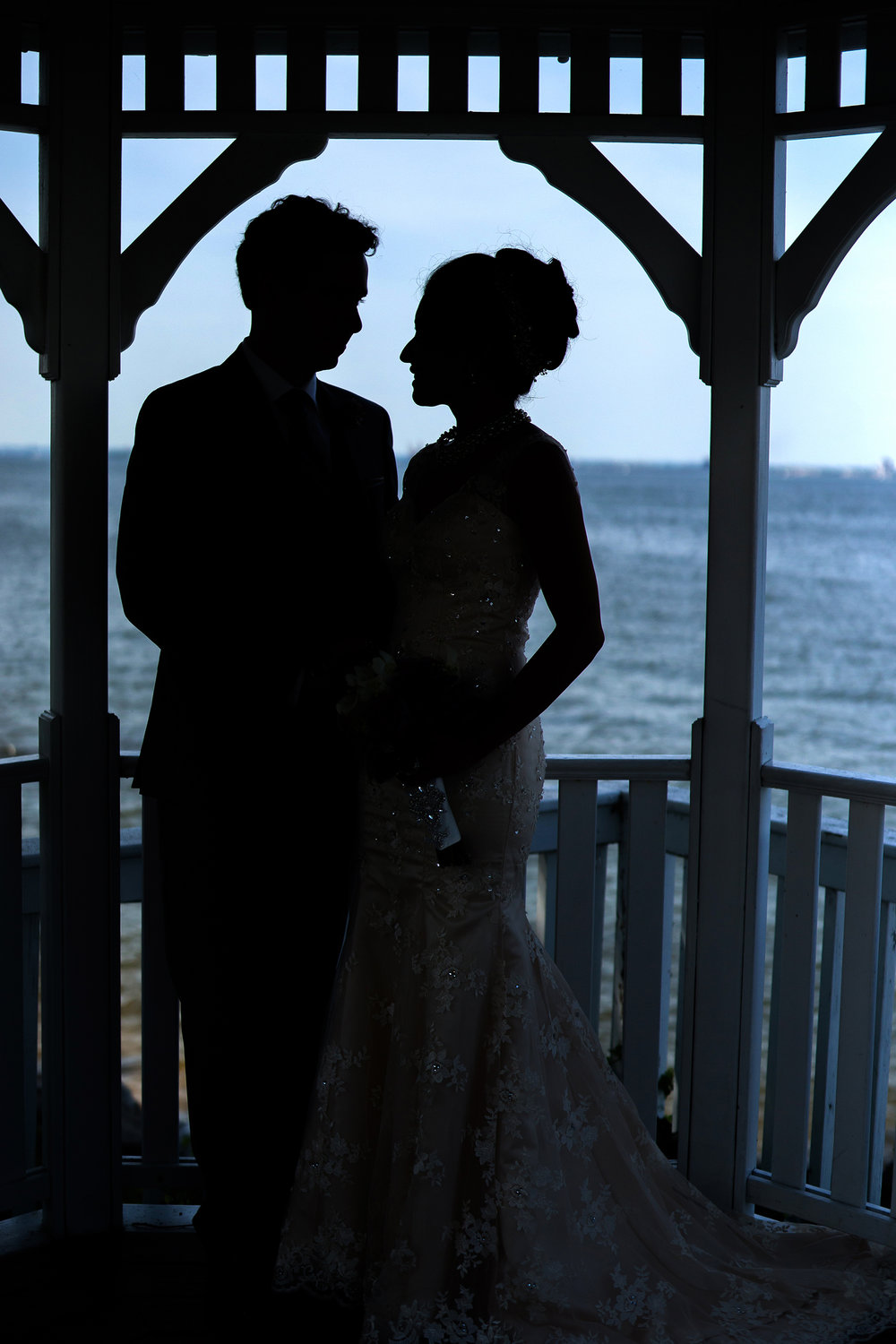 bride and groom silhouette on ocean celebrations at the bay