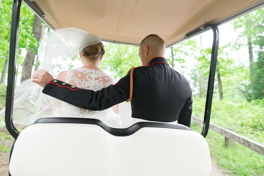 Bride and groom on a golf cart with the veil flying in the wind