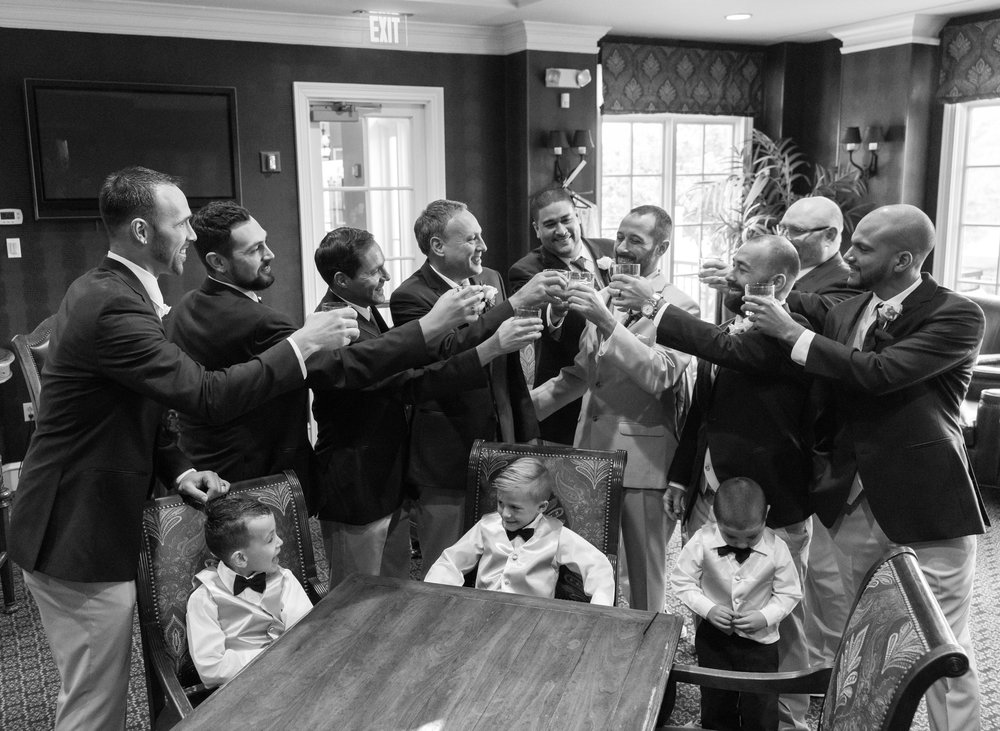 Groomsmen toasting each other in getting ready room