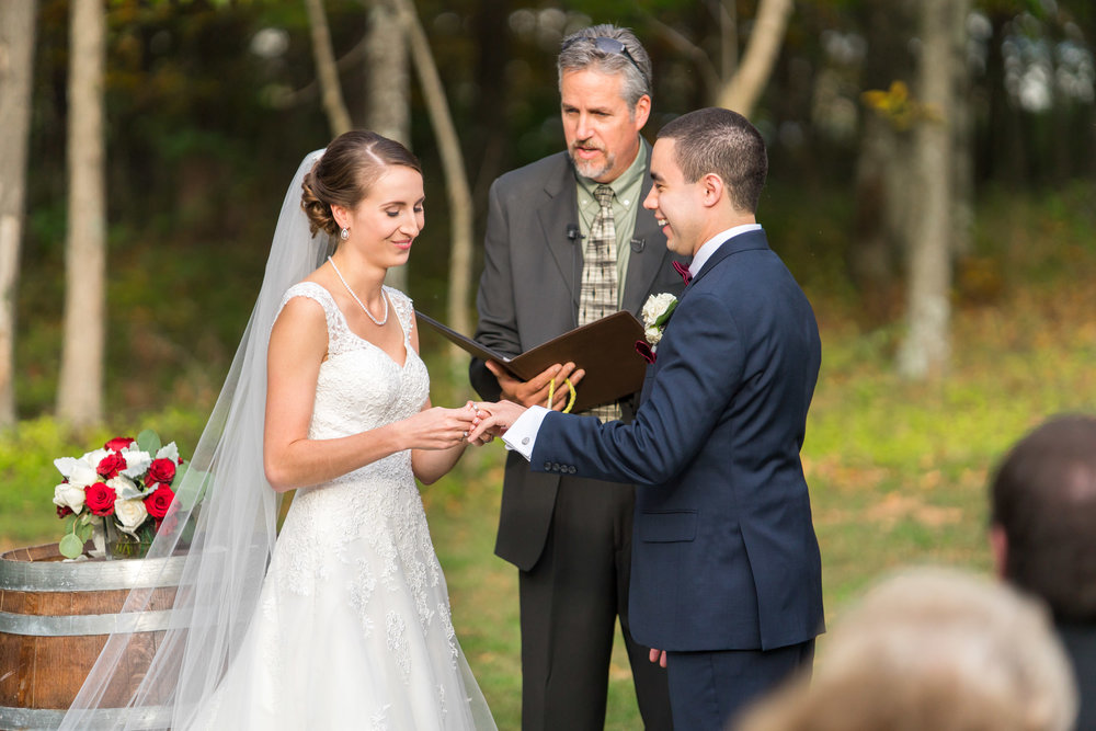 Bride and groom exchanging vows at outdoor ceremony.